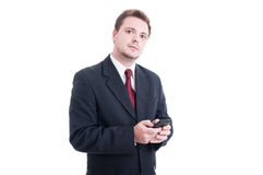 Business person holding and using smartphone. Looking to the camera isolated on white Royalty Free Stock Photography