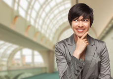 Business Person Inside Corporate Building Looking To The Side. Pretty Businesswoman Standing Inside Corporate Building Looking To The Side Royalty Free Stock Photo