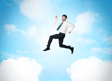 Business person jumping over clouds in the sky Stock Images
