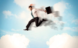 Business person jumping over clouds in the sky Stock Photo
