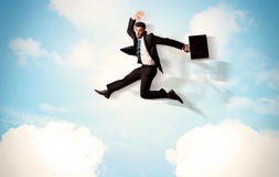 Business person jumping over clouds in the sky Royalty Free Stock Photo