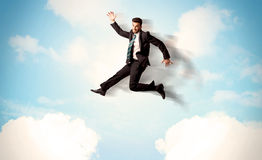 Business person jumping over clouds in the sky Royalty Free Stock Image