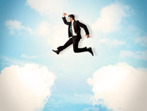 Business person jumping over clouds in the sky Stock Image