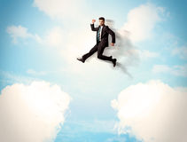 Business person jumping over clouds in the sky Royalty Free Stock Images