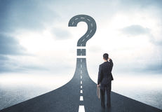 Business person lokking at road with question mark sign Royalty Free Stock Photo