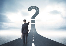 Business person lokking at road with question mark sign. Concept Stock Images