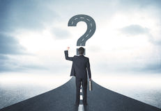 Business person lokking at road with question mark sign. Concept Royalty Free Stock Images