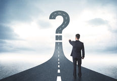 Business person lokking at road with question mark sign Royalty Free Stock Images