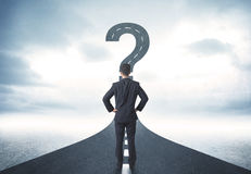 Business person lokking at road with question mark sign. Concept Stock Photography