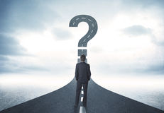 Business person lokking at road with question mark sign. Concept Stock Photos