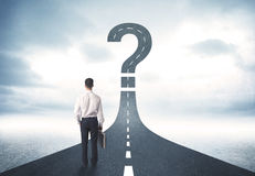 Business person lokking at road with question mark sign Royalty Free Stock Photography