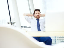 Business person looking at computer screen thinking. Caucasian businessman sitting at desk looking at laptop screen and thinking in office Royalty Free Stock Image