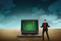 Business person looking giant laptop on the desert Stock Photos