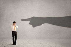 Business person looking at huge shadow hand pointing at him conc Royalty Free Stock Photo