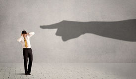 Business person looking at huge shadow hand pointing at him conc Royalty Free Stock Photos