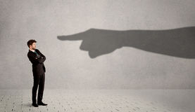 Business person looking at huge shadow hand pointing at him conc. Ept on background Royalty Free Stock Image