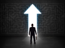 Business person looking at maze with solution arrow on the wall Royalty Free Stock Photos