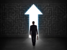 Business person looking at maze with solution arrow on the wall Royalty Free Stock Photo