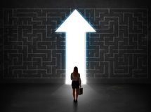 Business person looking at maze with solution arrow on the wall Stock Photography