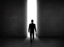 Business person looking at wall with light tunnel opening Royalty Free Stock Photography