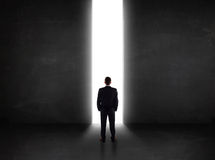 Business person looking at wall with light tunnel opening. Concept Stock Image