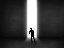 Business person looking at wall with light tunnel opening Royalty Free Stock Photos