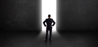 Business person looking at wall with light tunnel opening Royalty Free Stock Images
