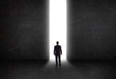 Business person looking at wall with light tunnel opening Royalty Free Stock Photo