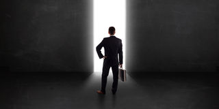 Business person looking at wall with light tunnel opening Royalty Free Stock Image