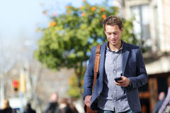 Business person man on mobile phone in city street. Business man using mobile phone walking to work. Young urban businessman professional on smartphone walking stock images