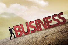Business person pushing 3D business word uphill Stock Photo