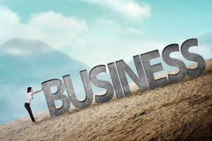 Business person pushing 3D business word uphill Royalty Free Stock Image