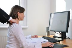 Business person receives massage. Business working person (woman) behind computer receiving neck massage from colleague (only hands visible Royalty Free Stock Photo