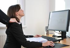 Business person receives massage from colleague. Business person (woman) on workplace with computer receiving neck massage from colleague (only hands visible Royalty Free Stock Photos
