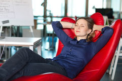 Business Person relaxing in red Chair at modern creative Office Royalty Free Stock Images