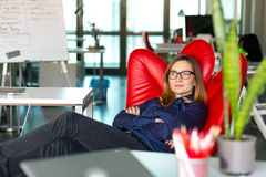 Business Person relaxing in red Chair at modern creative Office Royalty Free Stock Photo
