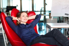 Business Person relaxing in red Chair at modern creative Office. Smiling successful Business Lady in red relaxation Office Chair inside modern creative Company Royalty Free Stock Photography