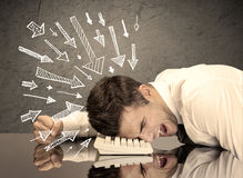 Business person resting his head on keyboard with pressure illustrated by arrows pointing at him concept. An exhausted business person resting his head on Stock Photo