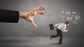 Business person running away from big hand Stock Photo