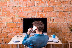 Business person sitting at office desk, talking on phone. Against brick wall. Computer on the table. Coffee cup, personal organizer and various office stuff Royalty Free Stock Photo