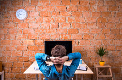 Business person sitting at office desk wearing smart watch. Business person sitting at office desk against brick wall. Smart watch on hand and computer on the Royalty Free Stock Images