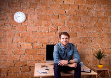 Business person sitting on office desk wearing smart watch. Hipster businessman sitting on office desk, smiling, against brick wall. Smart watch on hand and stock photo