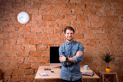Business person sitting on office desk wearing smart watch. Hipster businessman sitting on office desk, smiling, against brick wall. Smart watch on hand and royalty free stock photo