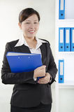 Business person standing and holding a document Stock Photography