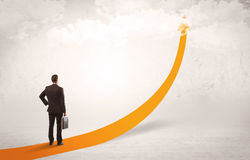 Business person standing on orange arrow Royalty Free Stock Images
