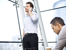 Business person talking on cellphone in office Royalty Free Stock Photography