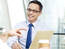 Business person talking in office. Caucasian business man holding tablet computer listening to someone and smiling during a conversation in office Royalty Free Stock Images