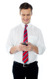 Business person texting. Happy business person busy texting against white background Stock Image
