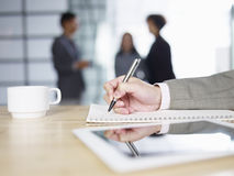 Business person thinking and writing. Close-up of male's hand writing on notepad with people talking in background Stock Photography