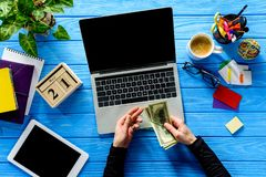 Business person tying dollars with rubber band by laptop on blue wooden table royalty free stock image